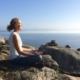 Anni sidder i meditativ stilling på en klippeafsats over havet