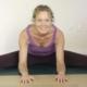 Anni laver yoga og ligger let foroverbøjet med udstrakte ben